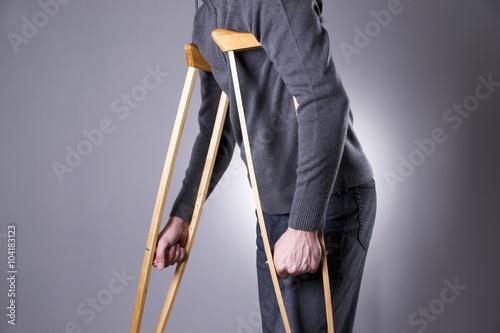 Vászonkép Man on crutches on a gray background