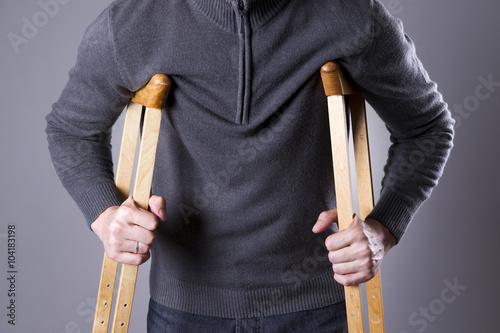 Valokuvatapetti Man on crutches on a gray background