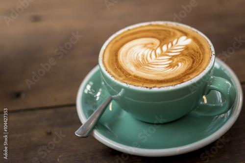 Valokuvatapetti hot cappuccino with latte art on wood background