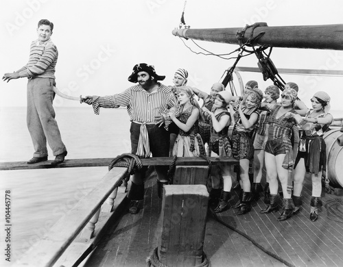 Group of pirates trying to push a young man over a plank Fototapeta
