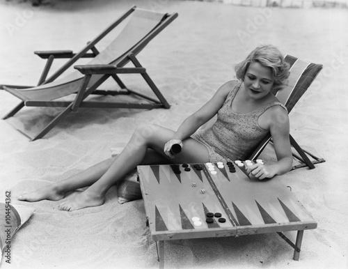 Woman playing backgammon on beach Fototapet