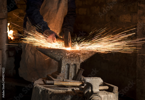 The blacksmith manually forging the molten metal on the anvil in smithy with spa Fototapeta