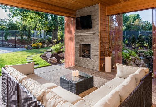 Fotografía Beautiful covered patio outside new luxury home with television, fireplace, and