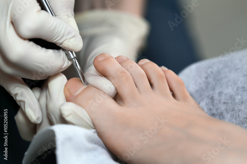 Close up pedicure process. Master working with cuticle remuver