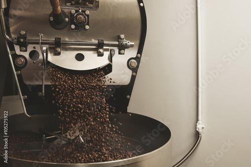 coffee beans fall from a large roaster machine Fototapeta