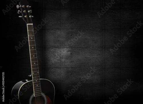 Fotografia Black acoustic guitar on dark black wooden background.
