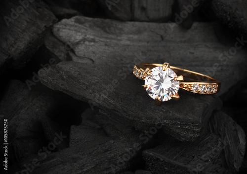 jewelry ring witht big diamond on dark coal background, soft foc