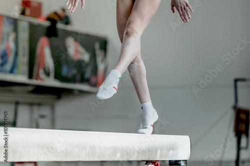 Obraz na plátně Dívka gymnasta sportovec během cvičení na kladině v gymnastických soutěžích