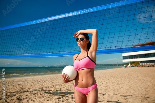 Obraz na plátně Mladá žena s volejbalovým míčem a branky na pláži