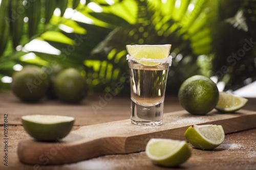 Obraz na płótnie Gold tequila shot with lime fruits