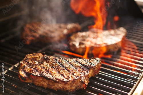 steaks cooking over flaming grill Fototapeta