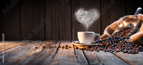 Fotografia Traditional Coffee Cup With Heart-Shaped Steam On Rustic Wood