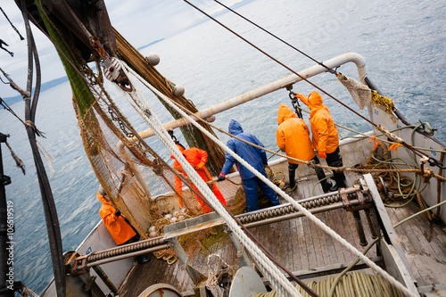 Photo Fishermen in protective suits on deck Fishing vessel
