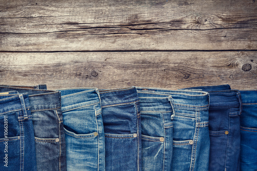 Canvas Print Fashion different jeans on wooden background. Retro toned.