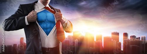Biznesmen superbohatera z zachodem słońca w mieście