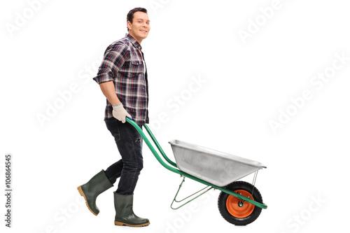 Stampa su Tela Gardener pushing an empty wheelbarrow