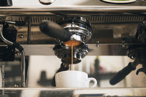 Fotografie, Obraz Fresh espresso coffee brewing through the bottomless portafilter in white ceramic cup in artisan cafe shop
