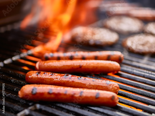 Fototapeta tasty hot dogs cooking on grill with hamburgers
