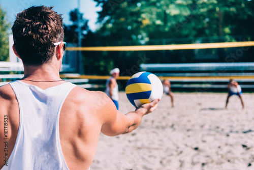 Beach volleyball player serving