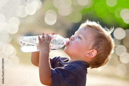 Valokuvatapetti beautiful blonde child drink water outdoor