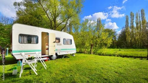 Fotografija White caravan trailer on a green lawn in a camping site