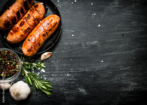 Fried sausages with garlic and herbs in a pan. Fototapeta