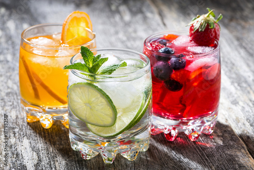 assortment of fresh iced fruit drinks on wooden background