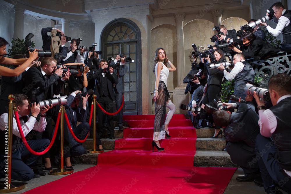Fotografowie na czerwonym dywanie robią zdjęcia aktorce <span>plik: #107938520 | autor: razoomanetu</span>