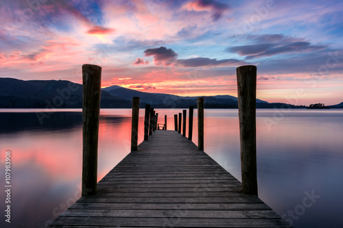 Tableau sur Toile Stunning vibrant pink and purple sunset on a beautiful evening at Ashness Jetty, Derwentwater, Lake District, UK