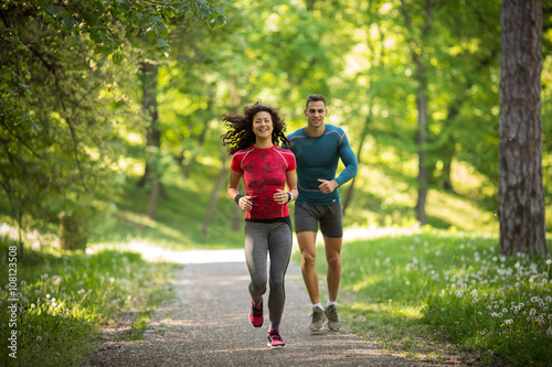 Photo Young couple jogging at the woods.Green environment.