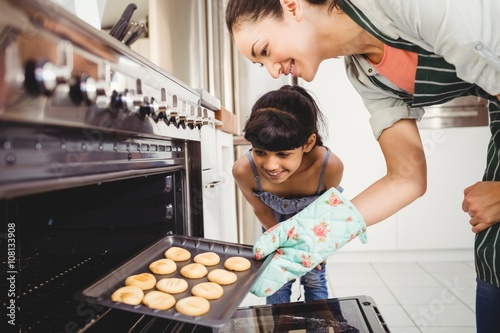 Mother and daughter placing cookies in oven Fototapet