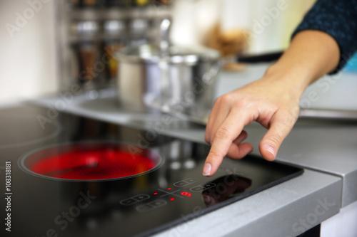 Female hand turns on electric hob closeup