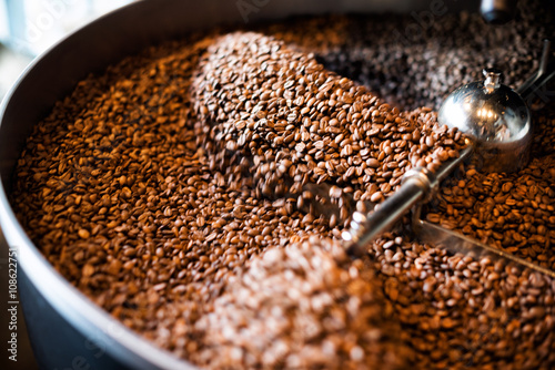 Freshly roasted coffee beans from a large roaster in the cooling cylinder Fototapeta