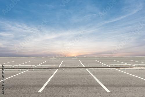 Fotografie, Obraz Prázdné parkoviště na pozadí při západu slunce