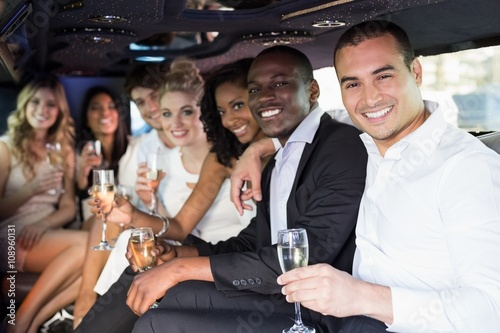 Canvas Print Well dressed people drinking champagne in a limousine