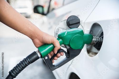Handle fuel nozzle to refuel the car. Fototapet