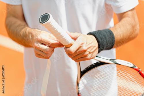 Canvas Print Putting new grip tape on tennis racket
