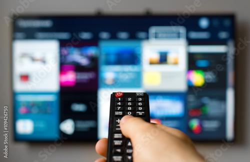 Obraz na płótnie Male hand holding TV remote control.
