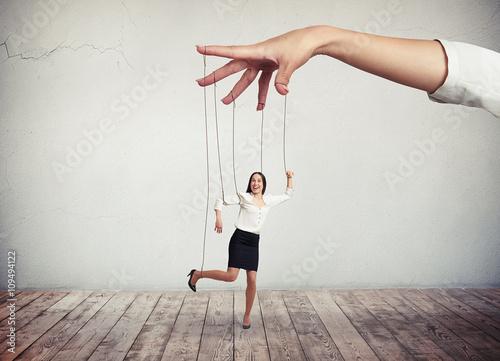 Fototapeta Woman looks like a puppet on strings