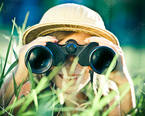 Fotografia beautiful young explorer girl with hat and binocular at park