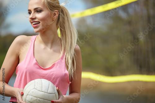 Fototapeta Radostné sexy blondýnka hraje volejbal venku na lakesi