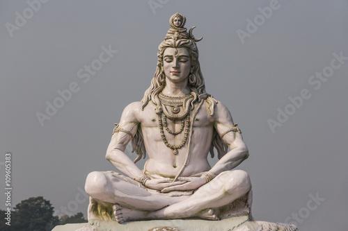 Canvas Print Hindu god Shiva sculpture sitting in meditation on Ganges river in Rishikesh, In