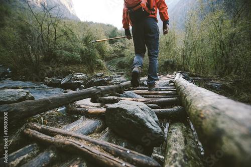Hiker crossing the bridge in Himalayas Fototapet