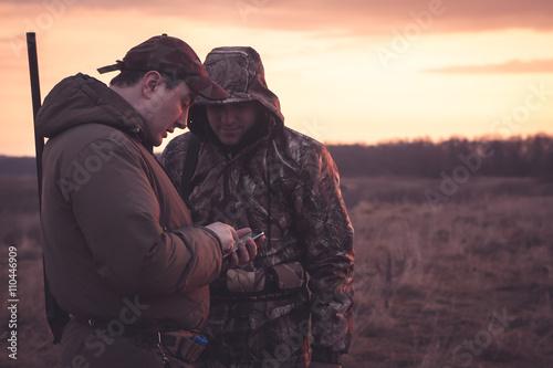 Hunters spot their position via smartphone in rual field during hunting season Fototapeta