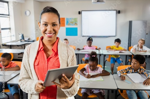 Fototapeta Miced race teacher posing in front of class with tablet pc