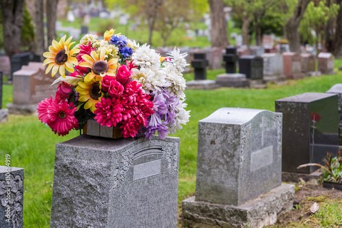 Obraz na plátne Flowers on a tombstone in a cemetary with headstones in the background