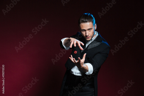 Photo Concentrated young man magician conjuring tricks with red dice