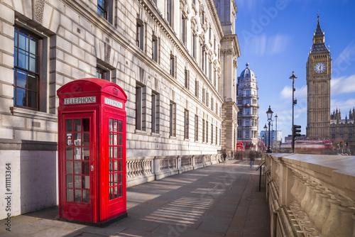 Fototapeta premium Tradycyjny czerwony brytyjski telefoniczny pudełko z Big Ben i Dwoistego Decker autobusem przy tłem na pogodnym popołudniu z niebieskim niebem i chmurami - Londyn, UK