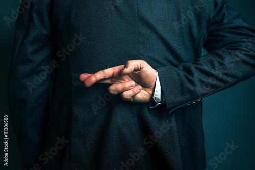 Billede på lærred Lying businessman holding fingers crossed behind his back