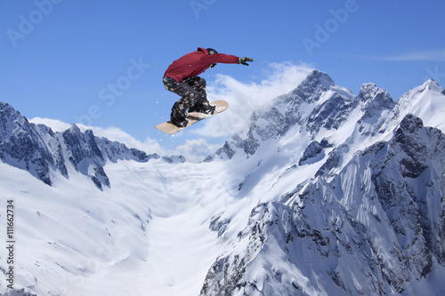 Canvas Print Snowboard rider jumping on mountains